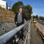 Standing on top of a half-finished retaining wall in Kaikorai Valley Rd is Dunedin businessman...