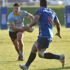 University midfield back Tyler Beary eyes up a gap as Harbour lock Sione Misiloi comes across at...