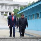 US President Donald Trump (L) and North Korean leader Kim Jong Un cross over a military...