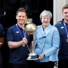England captain Eoin Morgan and Britain's Prime Minister Theresa May hold the trophy as they pose...