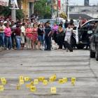People stand near bullet casings on the ground at a crime scene after a shootout in the...