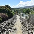 A digger clears debris from Roxburgh's Reservoir Creek after the November 2017 flooding in the...
