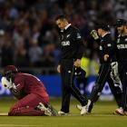 Carlos Brathwaite of the West Indies is consoled by New Zealand fielders Ross Taylor and Kane...