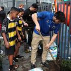 Otago outside back Josh Timu helps Koru School pupils in Auckland plant shrubs during the Mitre...