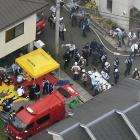 Rescue workers carry injured people from the three-story Kyoto Animation building which was...