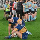 Taieri centre Matt Whaanga comforts team-mate Corey McKay while University players celebrate...