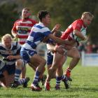 Clutha winger Kane Teunissen tries to run out of the tackle of Heriot's Blair Young and Luke...
