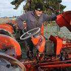Well-known vintage machinery enthusiast Barry Allison looks over a BMC mini tractor, which has...