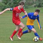 Caversham's Andrew Ridden (left) and Otago University's Edward Wilkinson compete for the ball...