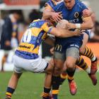 Otago midfield back Sio Tomkinson is tackled by Bay of Plenty first five-eighth Dan Hollinshead...