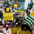 People hold flags and signs in solidarity with the people of Kashmir, during a rally in Karachi....