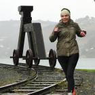 Cancer survivor Jannifer Palmer jogs past the Kuri Dog sculpture near the Otage Yacht Club...