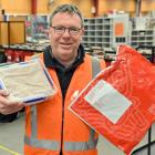 New Zealand Post Coastal Otago area manager Craig Strathern holds a mysterious homemade fruitcake...