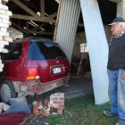 Ian Melton looks at the car which is still in his building in High St, Waimate, yesterday. PHOTO:...