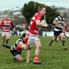 Clutha fullback Zak Thoms runs past his Crescent counterpart Jayden Sutton on the way grounds on...