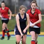 Otago Girls' High School hockey player Tessa Buschl (18), of Outram, dribbles a ball while being...