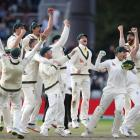Australian players celebrate taking the wicket of England's Craig Overton to win the match and...