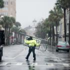 A police officer moves a traffic barrier amid wild weather in Charleston, South Carolina. Photo:...