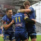 Sio Tomkinson and Michael Collins celebrate a try by Jona Nareki in an intense battle against...