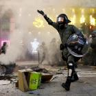 Riot police walk next to a street barricade during a demonstration in Mong Kok district in Hong...
