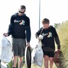 David Heads and son Aiden (11), of Dunedin, carry rubbish from the sand dunes at St Kilda during...