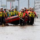Rescue workers in Nagano Prefecture carry a rubber dinghy as they search a flooded area in the...