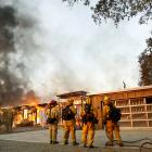 Firefighters look on as a house burns in the wildfires north of San Francisco Bay, California....