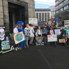 About 25 protesters are singing and holding placards outside Distinction Hotel where an...