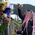 Tasha Gweshe (23), a student from a neighbouring flat, places flowers in the hedge at the flat in...
