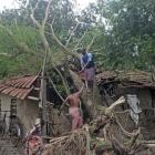 Men try to clear debris from their damaged house after Cyclone Bulbul hit the area in Namkhana,...