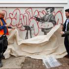 Men place a sheet over a Banksy mural known as The Painter, which first appeared in 2008, before...