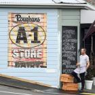 Blacks Road Green Grocer owner Christopher Wilson admires a recently uncovered sign on his 100...