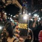 Pro-democracy supporters hold their phone flashlights at a rally to show support for students at...