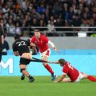 New Zealand's Anton Lienert-Brown tries to break away from Wales' Hallam Amos. Photo: Getty