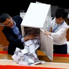 Officials open a ballot box at the polling station in the South Horizons West district as voting...