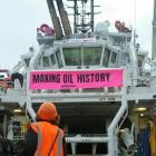 An environmental protester stands on the deck of offshore supply vessel Skandi Atlantic in front...