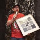 Teacher and musician Brendan Christie accepts an artwork by Dunedin visual artist Lynn Taylor, to...