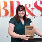 Barr Burgess and Stewart managing director Christine McNamara holds an old staff handbook. Photo:...