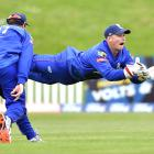 Auckland wicketkeeper Glenn Phillips catches out Otago batsman Neil Broom while watched by Martin...