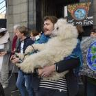 Jack Brazil and his standard poodle Saffron Squish join other demonstrators protesting against an...
