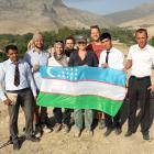 Local school teachers pose with the academics who worked on the site, and an Uzbek flag.