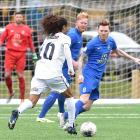 Southern United defenders Stephen Last (left) and Danny Ledwith look to stop Auckland City's...