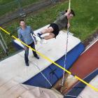 Cole Gibbons goes over the pole while his father and coach Paul watches at the Caledonian Ground...