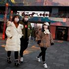People wearing face masks walk past luxury boutiques in the Sanlitun shopping district in Beijing...