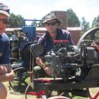 Ian Fyfe and Paul Gray tinker with a three-horsepower Hornsby stationary engine during an open...