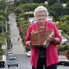Coleen Williamson hefts some of her front wall which was smashed by a bus in Baldwin St. Photo:...