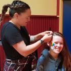The Mack volunteer hairdresser Justine Beer-Williams braids the hair of Milton Free Day attendee...