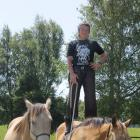 Cowboy Challenge host Bev Williamson shows off a challenge by standing on her purebred quarter...