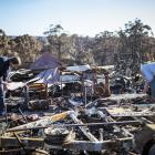 Brian and Elizabeth Blakeman inspect the bushfire damage to their property in Wairewa, Australia,...