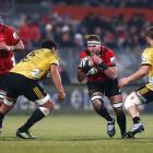 Kieran Read of the Crusaders runs at Isaia Walker-Leawere and Dane Coles of the Hurricanes...